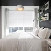 Белая кровать и серые стены