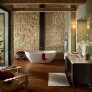 Интереьр ванной комнаты с одной стеной, декорированной светлым камнем