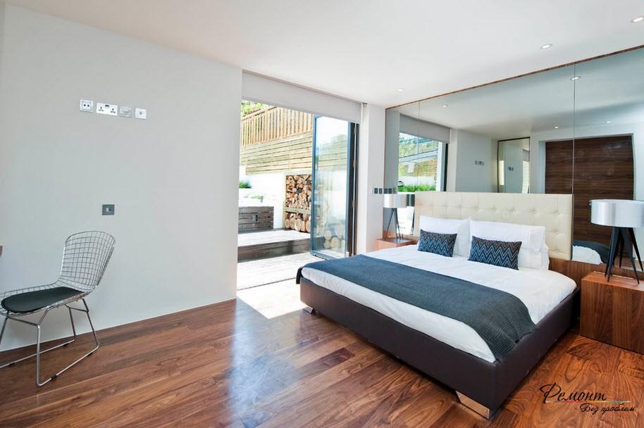 Темно-серый плед и подушки на белой кровати