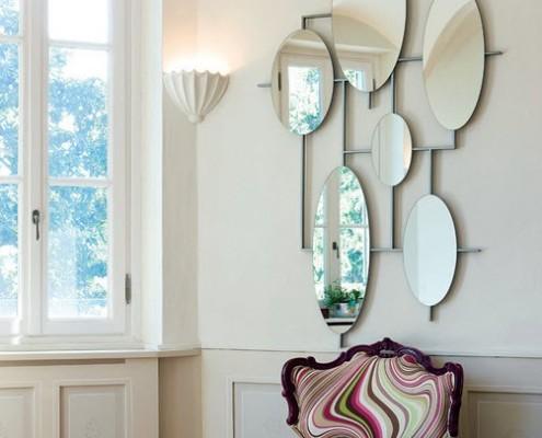 Несколько овальных зеркал на стене