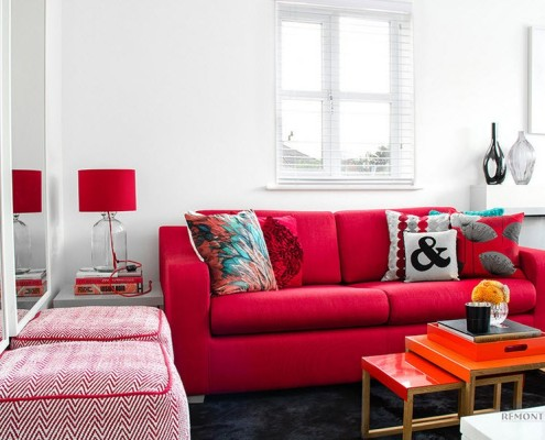 Красный диван возле зеркала