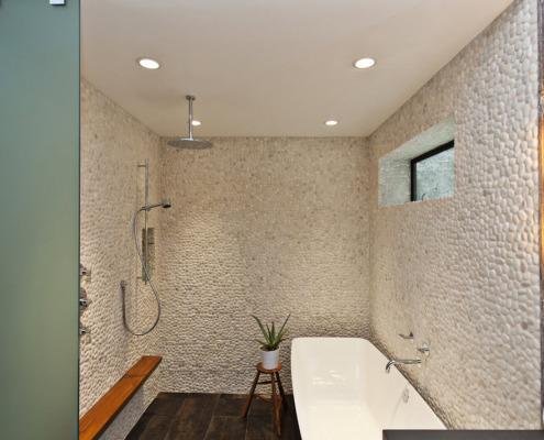 Галька на стене в ванной, покрытая белой краской