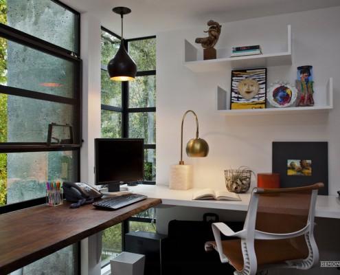 Коричневый и белый столы возле углового окна