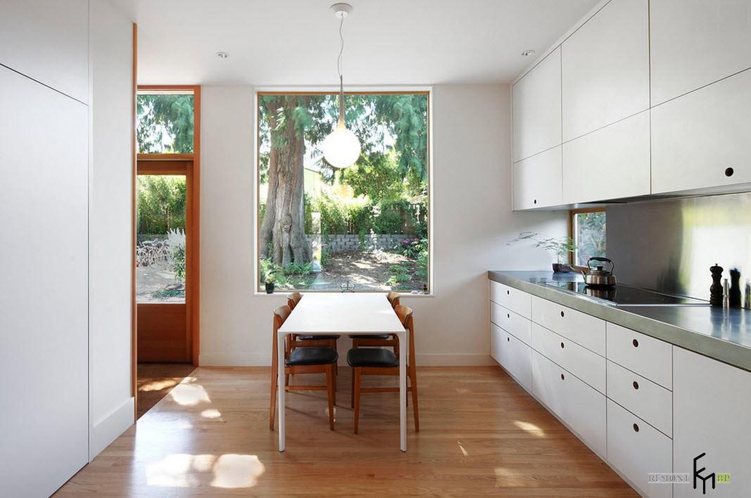 Продолговатый стол возле окна на кухне