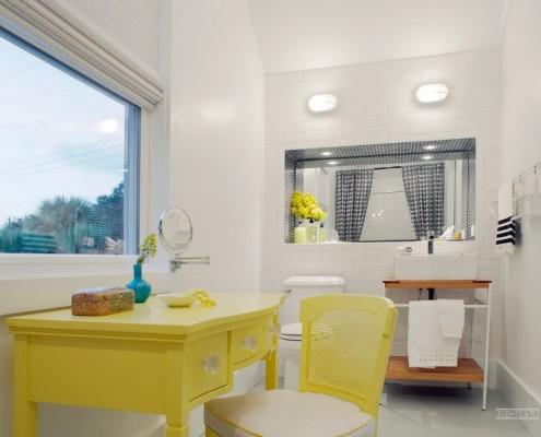 Желтый туалетный столик под окном в ванной