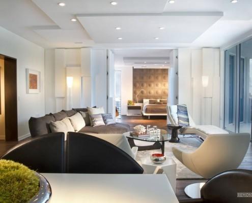 Трехслойный потолок и черный диван в гостиной