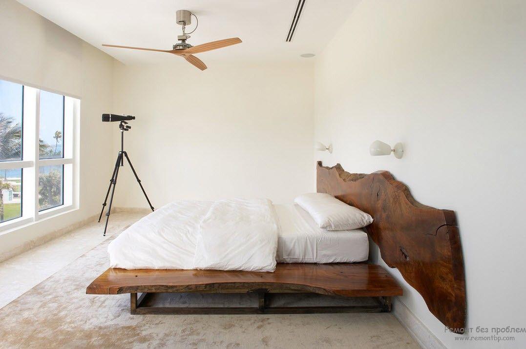 Светлый интерьер спальни с контрастной темной деревянной кроватью