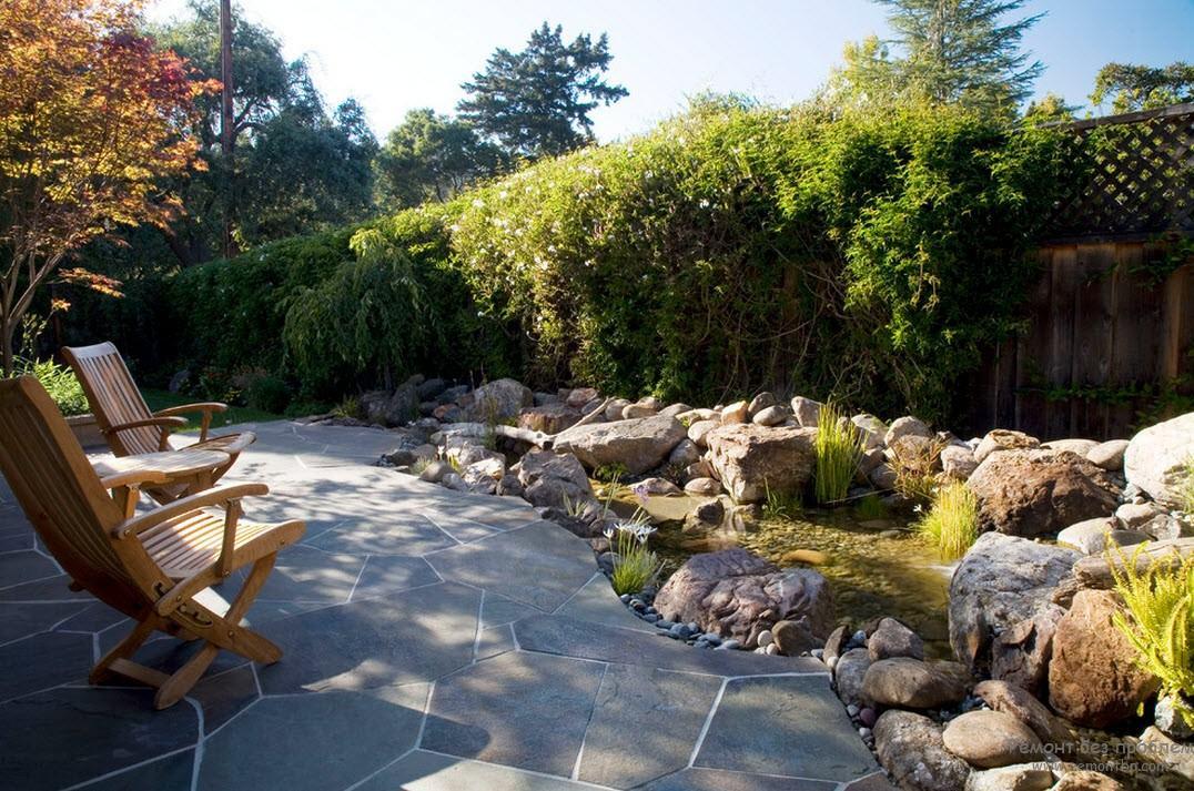 Неглубокий ручей, текущий среди крупных камней, прилегающая площадка, выложенная по контрасту с шершавыми валунами гладкими плитами, создают необычную композицию