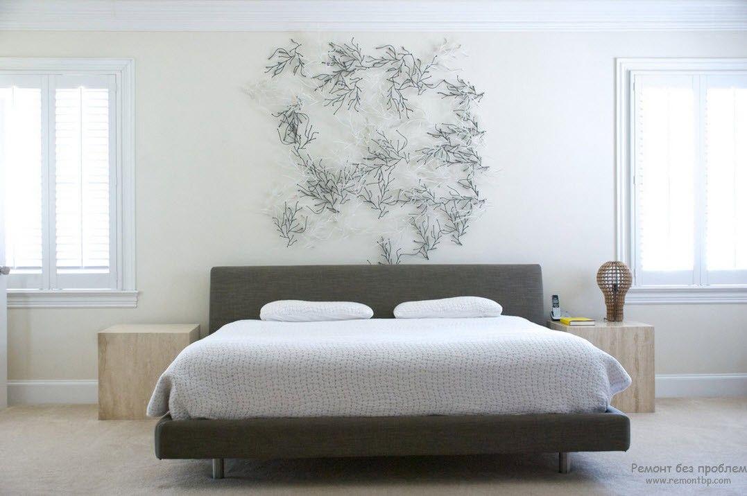 Низкая темная кровать в белой спальне