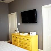 Желтый комод в оливковой спальне