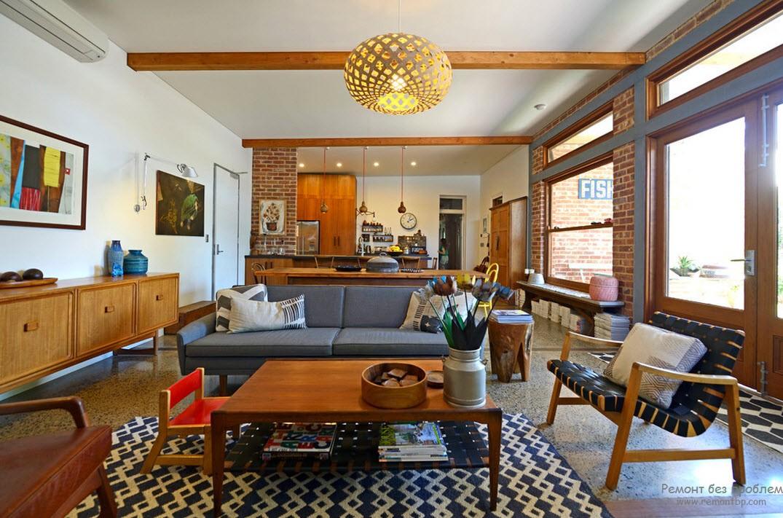 Промышленный стиль. Кроме обычной деревянной мебели столик в виде корявого пня. Сине-белый ковер сочетается с обшивкой диванов и кресел. Цветы в бидоне искусственные