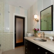Темная дверь в гармонии с мебелью в интерьере светлой ванной комнаты