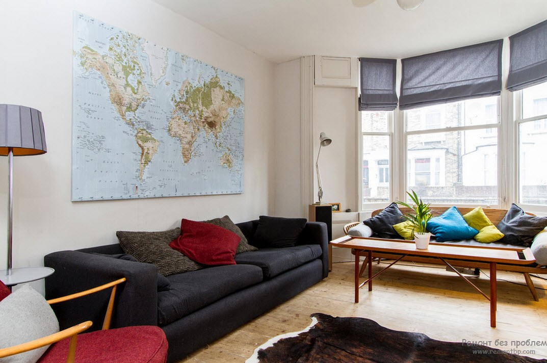 Комнату украшает карта на стене, цветные подушки и шкура на полу