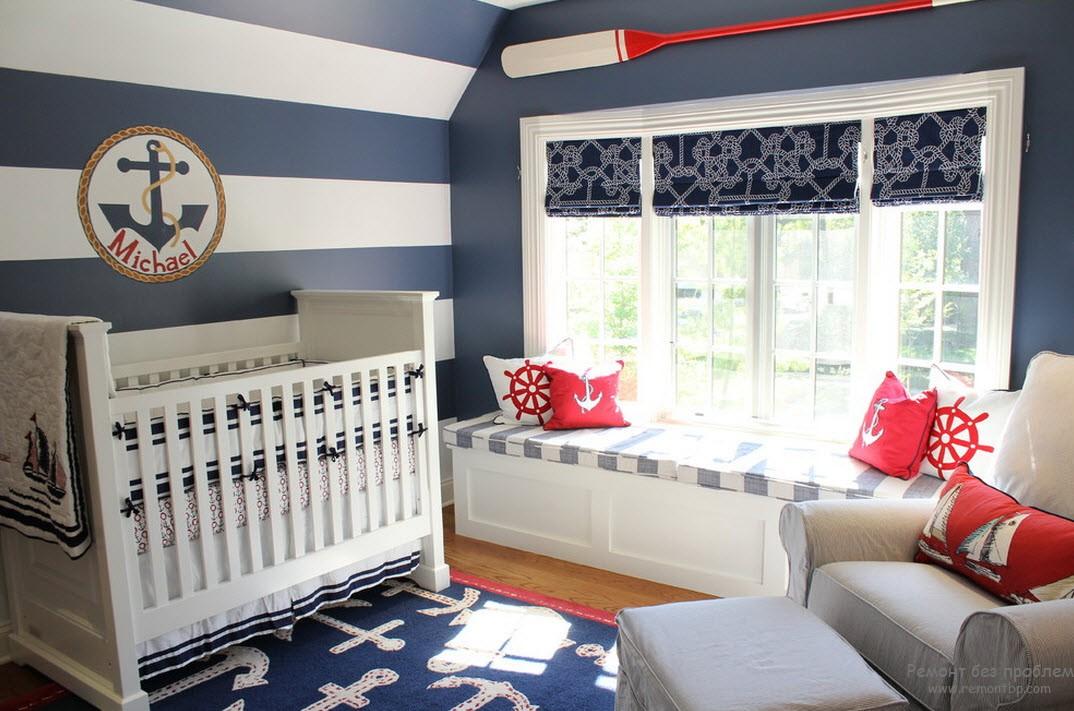Красные подушки с якорями освежают  сине-белый интерьер