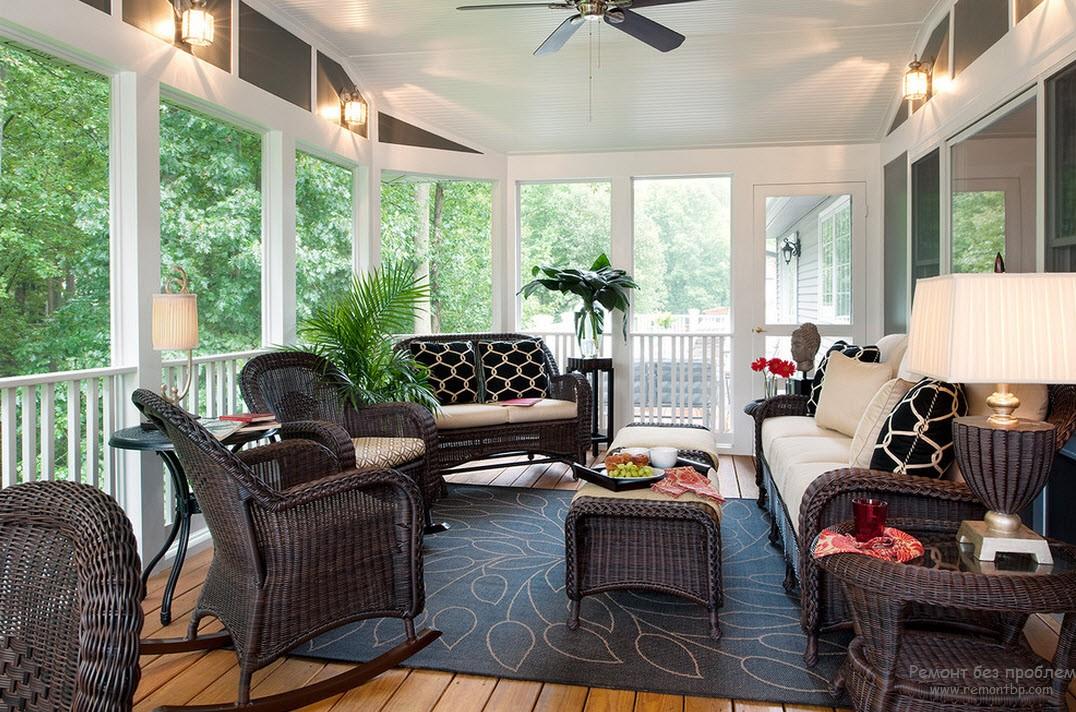 Урасивый интерьер веранды с плетеной мебелью и креслом-качалкой