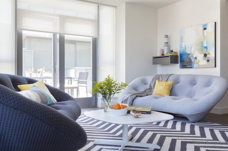 Сине-белый ковер и диваны волнообразной формы с подушками солнечного цвета
