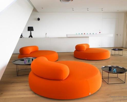 Зона семейного отдыха с ярко-оранжевой круглой мебелью