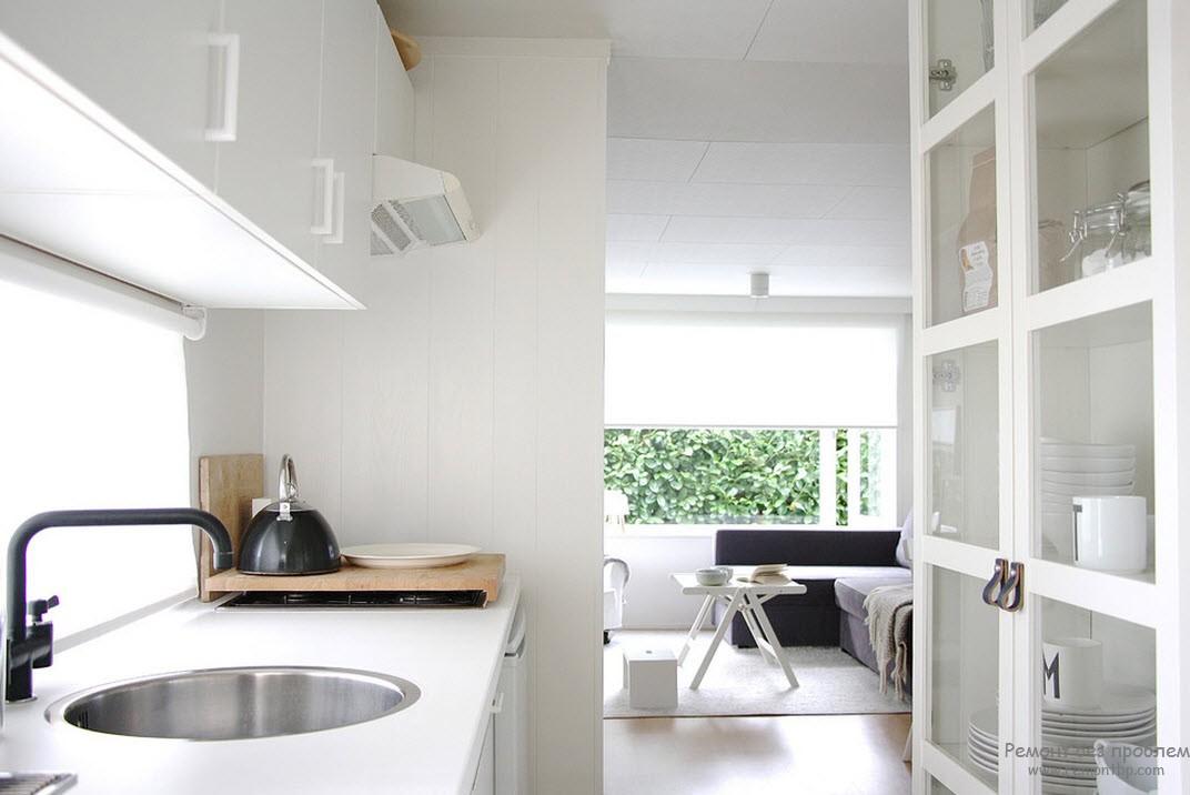 В белой кухне и столовой черный чайник и темные диваны