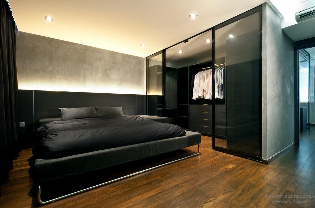 Отгороженная стеклом гардеробная в просторной спальной комнате
