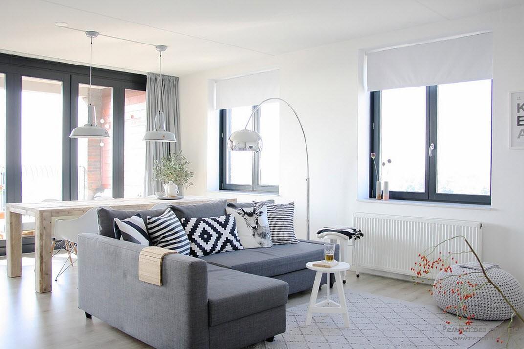 Серо-голубой угловой диван с разнообразными подушками белого с черным цветов