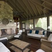 Очень просторная веранда с фукдаментальным камином и диваном-качелями в интерьере