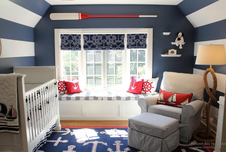 Сине-белые стены и красные подушки с изображением якорей и штурвалов