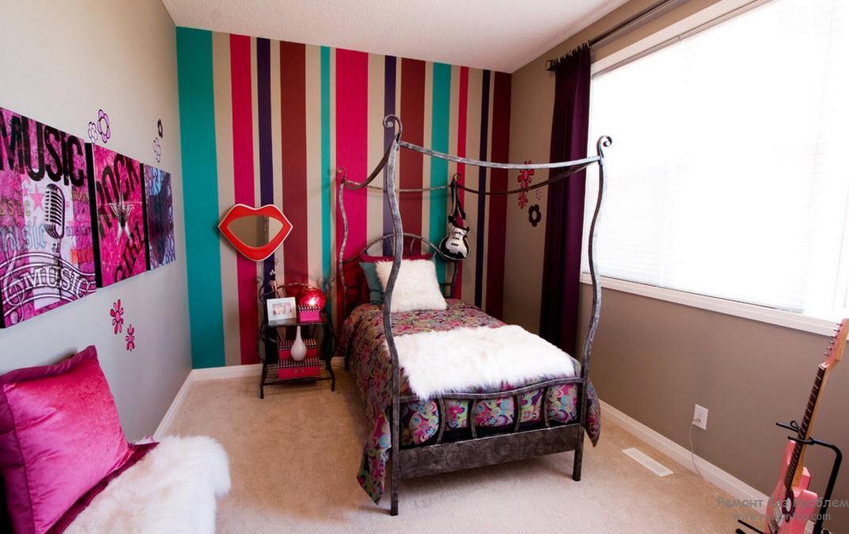 Акцент комнаты - стена, декорированная яркими полосами, гармонирующими с яркими аксессуарами на стене