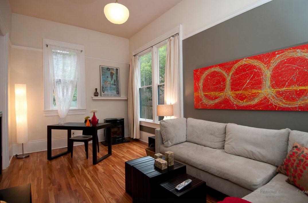 Красный цвет в интерьере серой гостиной использован в качестве отдельных акцентов
