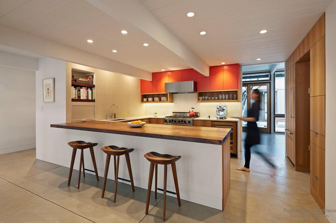 Оранжевые навесные шкафчики выполняют роль акцента интерьера кухни