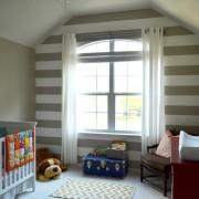 Одна стена детской комнаты декорирована широкими горизонтальными полосами