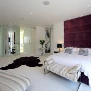 Белый ковер и фиолетовая стена в спальне
