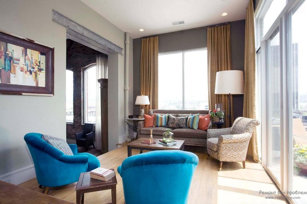 Два ярко-голубых кресла разбавляют серый интерьер гостиной