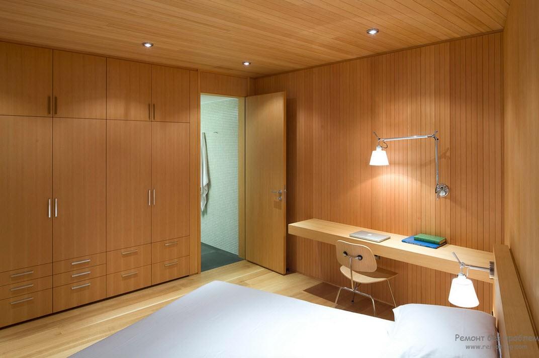Деревянная матовая поверхность встроенных шкафов-купе в деревянном интерьере домашнего кабинета