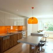 Оранжевые фартук и подвесной светильник в интерьере светлой кухни