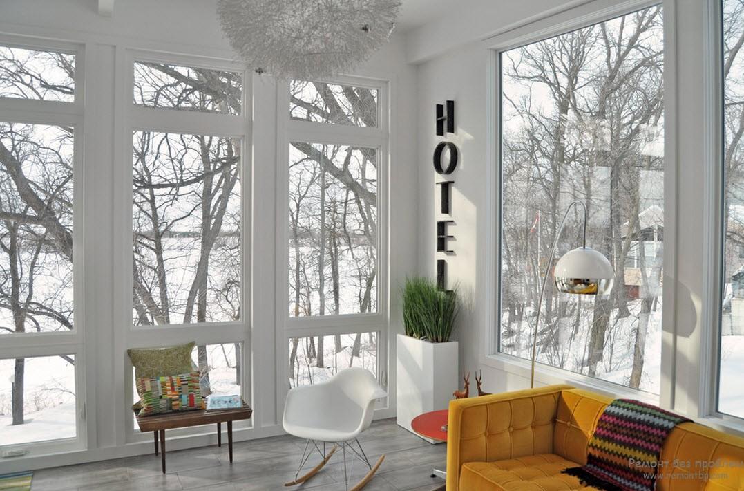 Приглушенный оранжевый цвет дивана и маленький красный столик согревают холодный холл