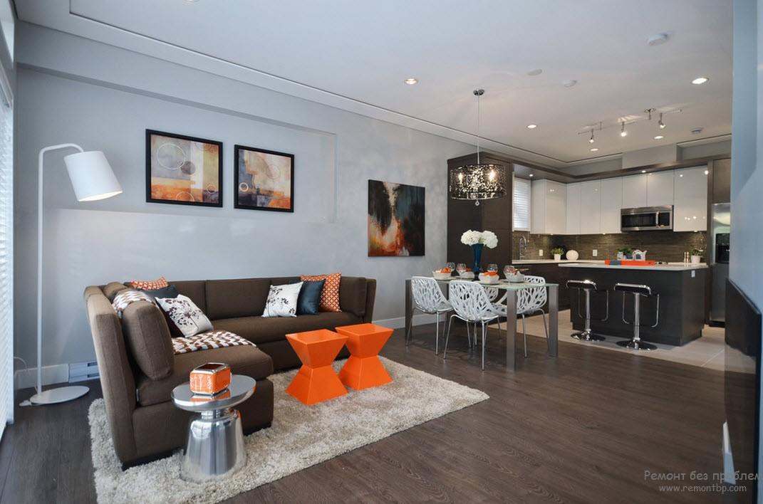 Яркие оранжевые акценты в интерьере коричневой гостиной