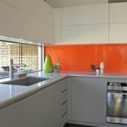 Оранжевый цвет в интерьере кухни использован только для фартука