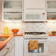 В качестве оранжевых акцентов использована столешница, кофейник и вазочка с мандаринами