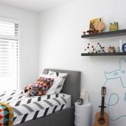 Белый интерьер комнаты для мальчика, разбавленный цветными аксессуарами