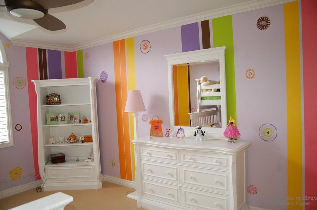 Вертикальные полосы ярких цветов чередуются с узором на стенах детской комнаты