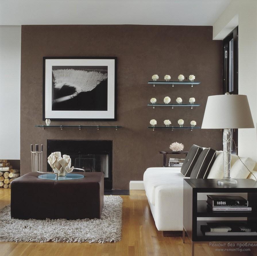 Одна стена гостиной темно-коричневая, на фоне которой светлые аксессуары