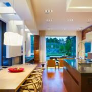 Изящная люстра и точечные светильники по периметру кухонной и гостинной зон
