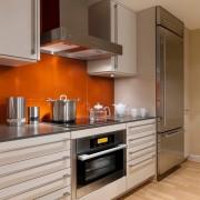 Оранжевый фартук в сочетании с белым и серым оттенками в интерьере кухни