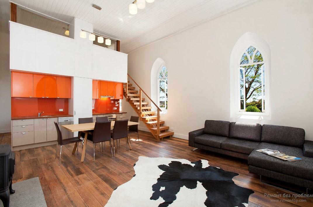 Интерьер оранжево-белой кухни, совмещенный с гостиной