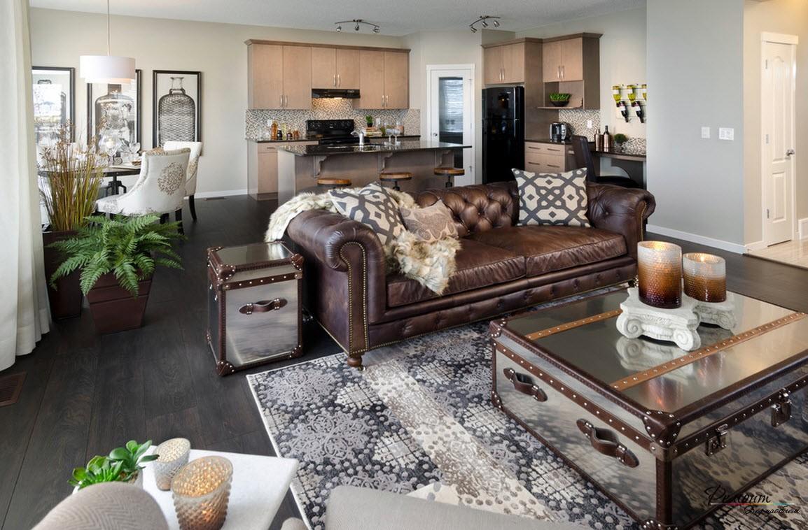 Интерьер просторной загородной гостиной=кухни-столовой с красивым кожаным диваном