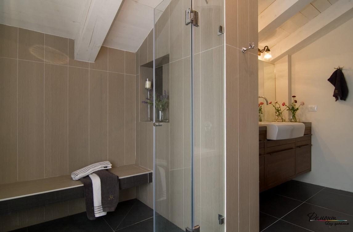 Темная квадратная плитка на полу и положенная вертикально более светлая на стенах сделали помещение с низким потолком более высоким