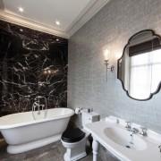 Эфффектный интерьер черно-белой ваннй комнаты с серыми обоями на стенах