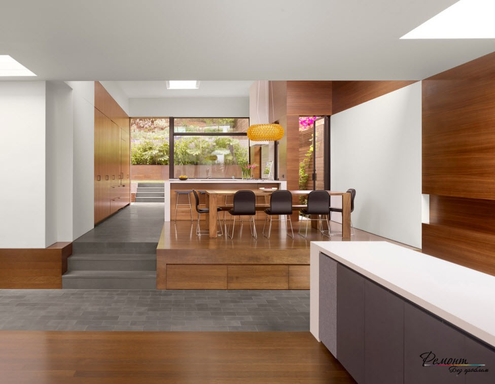 Зона столовой, размещенная на подиуме, является доминирующей в интерьере