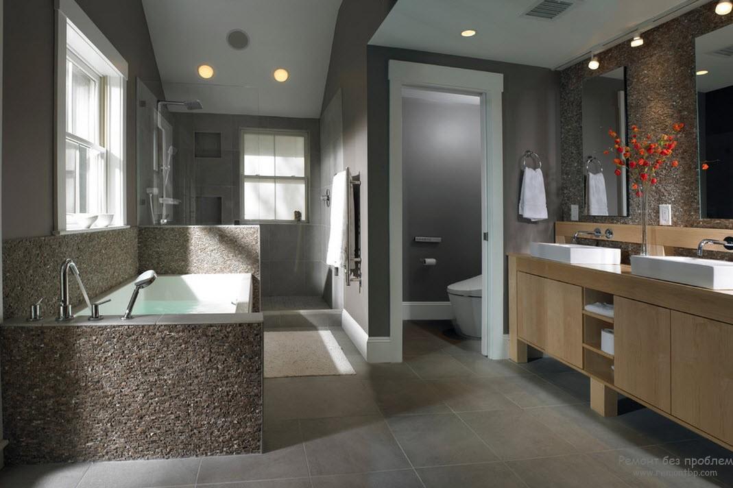 Отделка камнем, а также дерево в интерьере серой ванной комнаты служат оживляющими элементами
