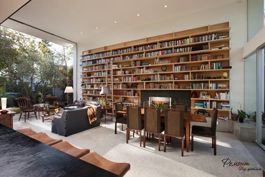 Очень стильный интерьер просторной гостиной с целой книжной стенгой